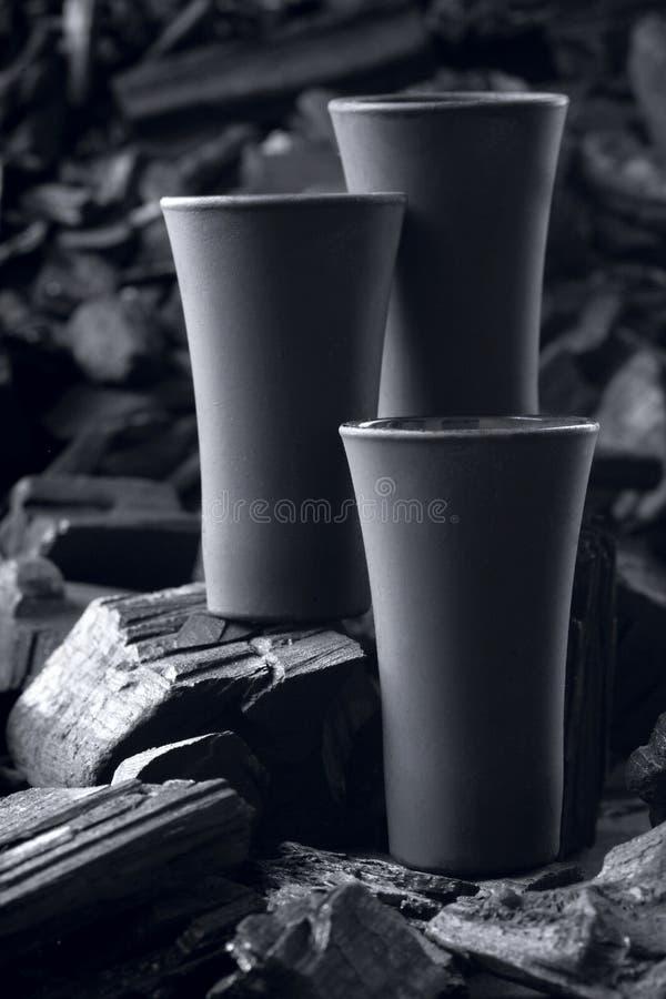 Μαύρο πυροβοληθε'ν γυαλί τριών μεταλλινών Στο υπόβαθρο ξυλάνθρακα Μαύρη έκδοση δημιουργικός Πιείτε Ευθυμίες Πρότυπο διάστημα αντι στοκ φωτογραφίες