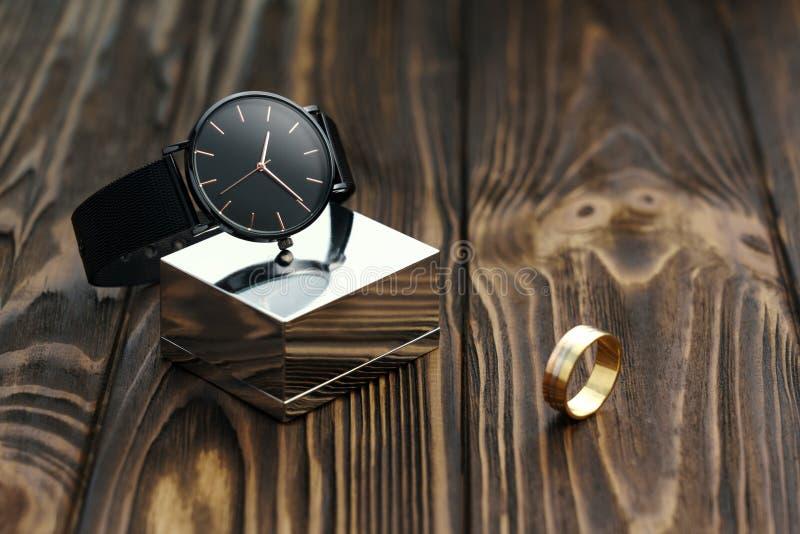 Μαύρο σύγχρονο wristwatch στον κύβο χρωμίου με το χρυσό δαχτυλίδι στο ξύλινο υπόβαθρο στοκ φωτογραφίες με δικαίωμα ελεύθερης χρήσης