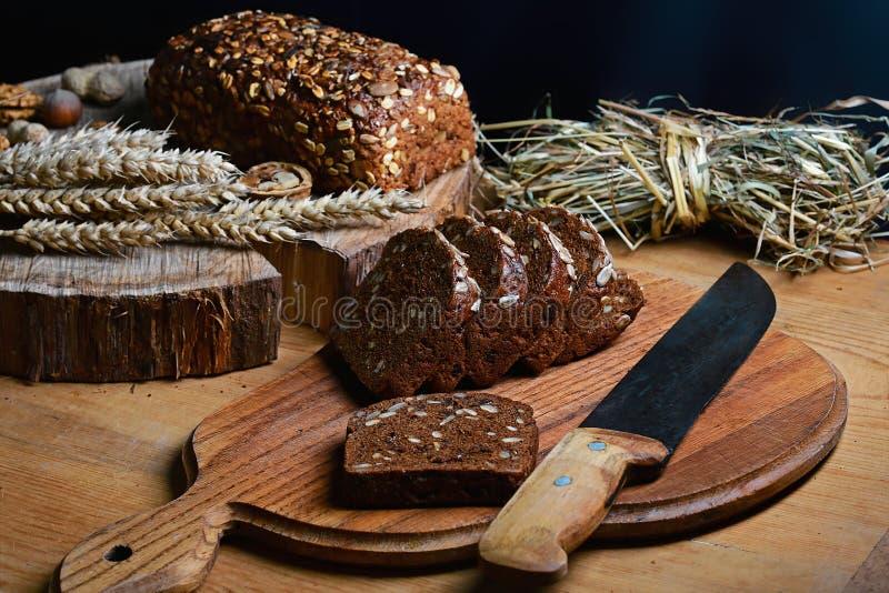 Μαύρο τεμαχισμένο ψωμί στον πίνακα, εκλεκτής ποιότητας μαχαίρι στον πίνακα και ένα ξύλινο υπόβαθρο σε ένα κολόβωμα, έννοια της υγ στοκ εικόνες με δικαίωμα ελεύθερης χρήσης