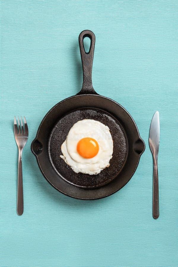 Μαύρο τηγανίζοντας τηγάνι με τα ανακατωμένα αυγά, δίκρανο, μαχαίρι στο τυρκουάζ τραπεζομάντιλο στοκ φωτογραφίες με δικαίωμα ελεύθερης χρήσης