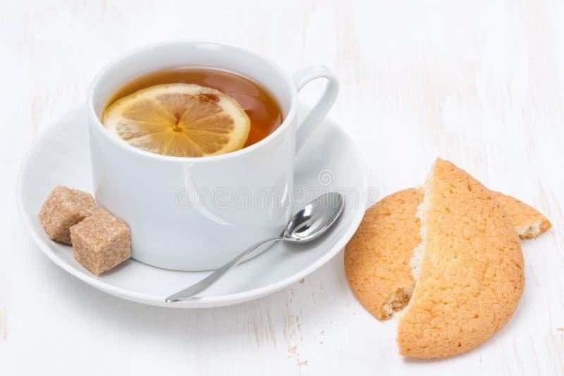 Μαύρο τσάι με το λεμόνι και μπισκότα στον άσπρο ξύλινο πίνακα στοκ φωτογραφία με δικαίωμα ελεύθερης χρήσης