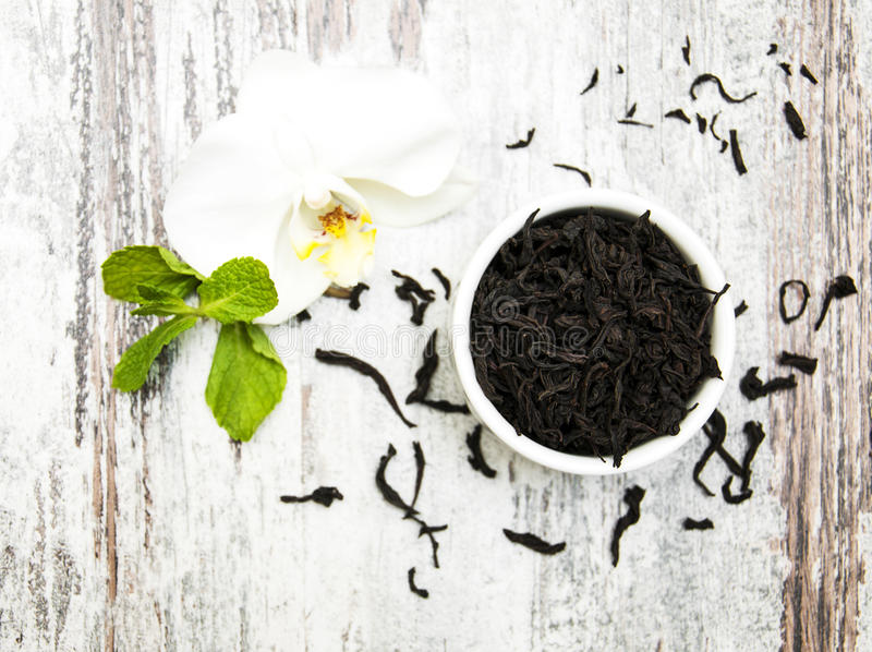 Μαύρο τσάι με το λουλούδι ορχιδεών στοκ φωτογραφίες