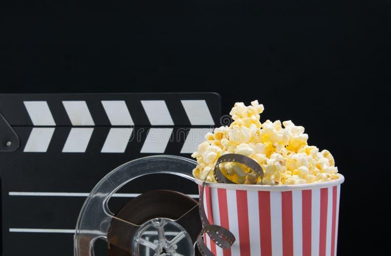 Μαύρο υπόβαθρο, ένας κάδος popcorn, ταινία, διπλάσιο για τη μαγνητοσκόπηση, στο φραγμό στον πίνακα στοκ εικόνες