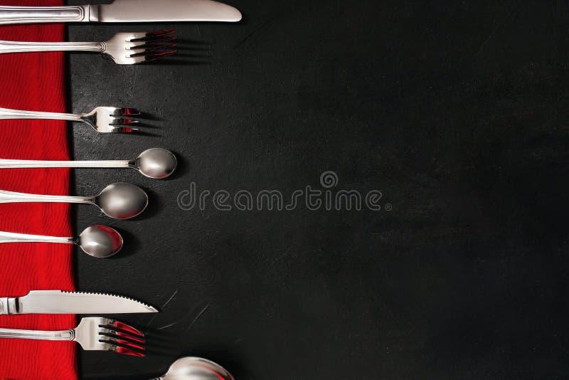 Μαύρο υπόβαθρο φιλοξενουμένων συμποσίου μαχαιροπήρουνων καθορισμένο στοκ φωτογραφία