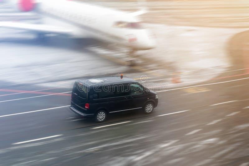 Μαύρο φορτηγό VIP υπηρεσιών που τρέχει στον τροχόδρομο αερολιμένων με το θολωμένο ιδιωτικό αεριωθούμενο αεροπλάνο στο υπόβαθρο Υπ στοκ εικόνα με δικαίωμα ελεύθερης χρήσης