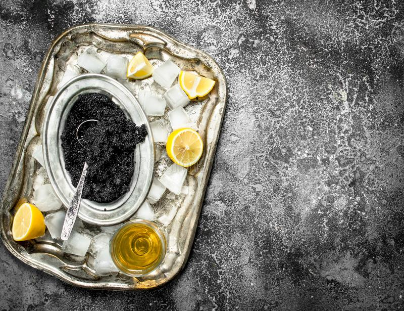Μαύρο χαβιάρι με το άσπρες κρασί και τις φέτες του λεμονιού στοκ εικόνες