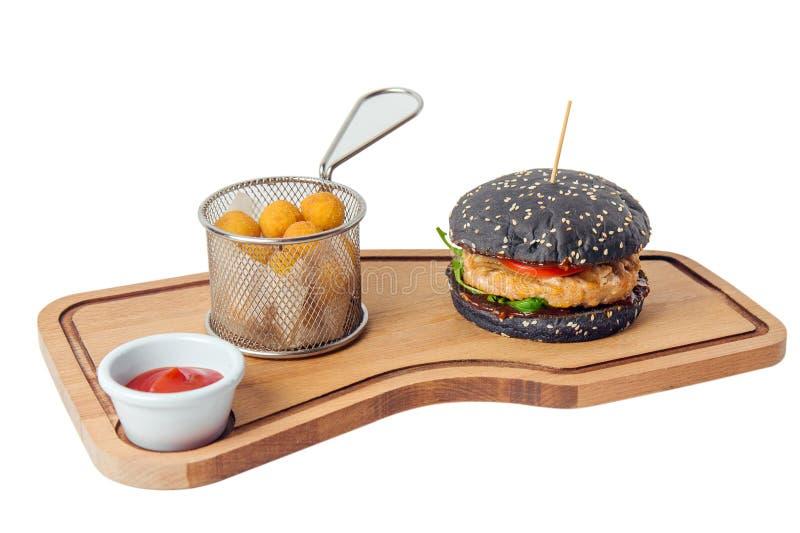 Μαύρο burger κοτόπουλου με τις σφαίρες τυριών στον τέμνοντα πίνακα που απομονώνεται στο άσπρο υπόβαθρο στοκ εικόνες