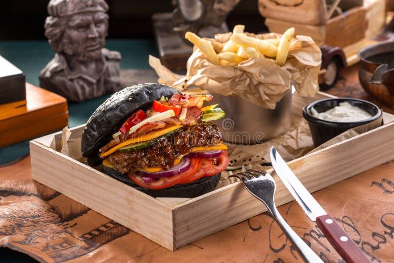 Μαύρο burger με τις τηγανιτές πατάτες στο ξύλινο κιβώτιο στον παλαιό χάρτη bavkground στοκ φωτογραφία