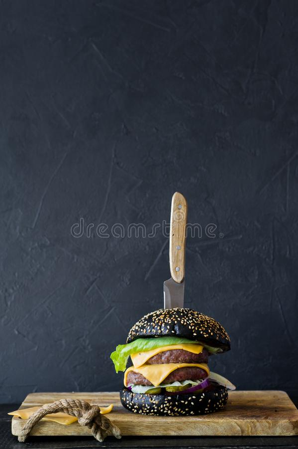 Μαύρο Burger σε έναν ξύλινο τεμαχίζοντας πίνακα Πλάγια όψη, μαύρο υπόβαθρ στοκ φωτογραφία με δικαίωμα ελεύθερης χρήσης