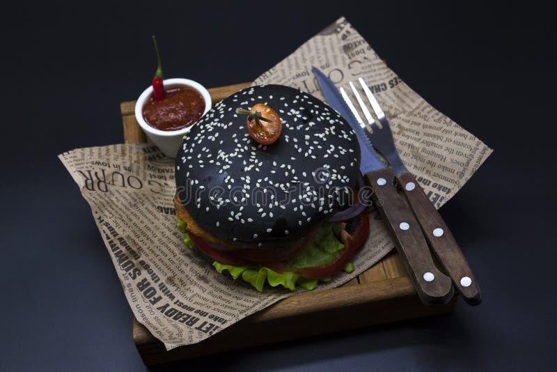 Μαύρο burger Burger με φέτες τις μαύρες ρόλων του juicy μαρμάρινου βόειου κρέατος, του λιωμένου τυριού, της φρέσκων σαλάτας και τ στοκ φωτογραφίες με δικαίωμα ελεύθερης χρήσης