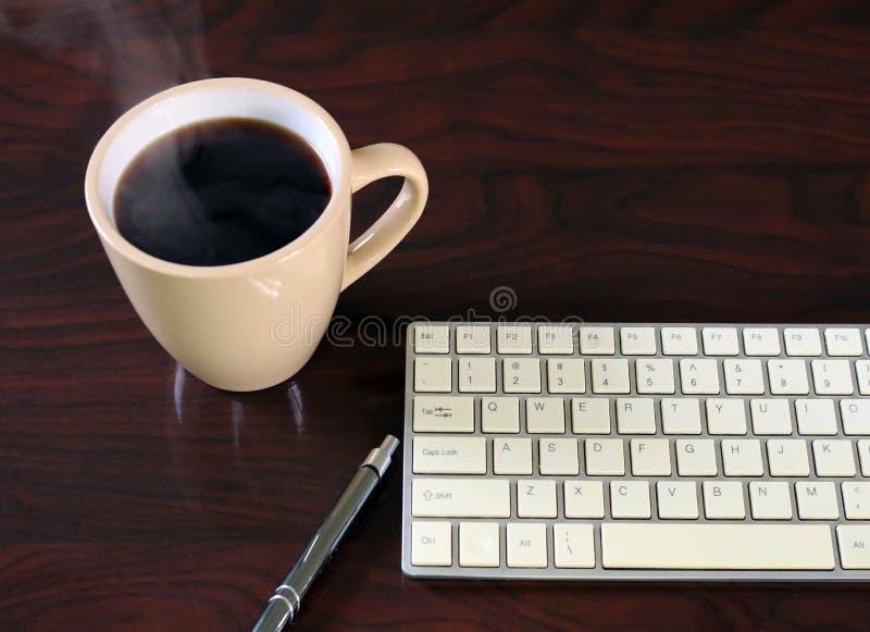 Μαύρο coffe σε μια μπεζ κούπα με το πληκτρολόγιο στον ξύλινο πίνακα στοκ φωτογραφία