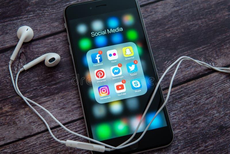 Μαύρο iPhone της Apple με τα εικονίδια των κοινωνικών μέσων και της άσπρης κάσκας στοκ εικόνες