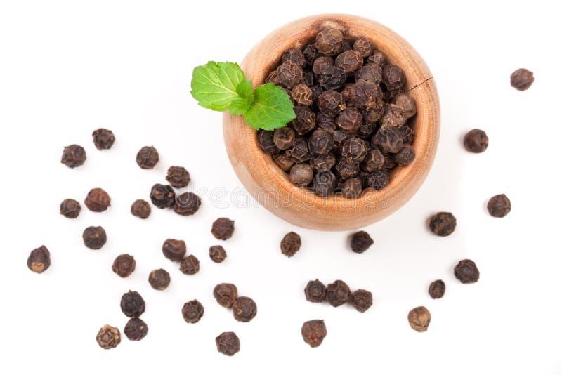 Μαύρο peppercorn σε ένα ξύλινο κουτάλι που απομονώνεται στο άσπρο υπόβαθρο Τοπ όψη στοκ φωτογραφίες