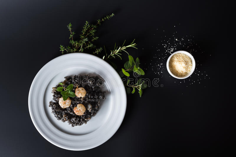 Μαύρο risotto με τα χορτάρια και την παρμεζάνα στοκ εικόνα