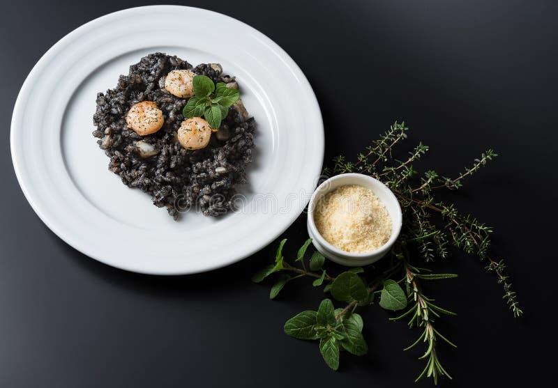 Μαύρο risotto με τα χορτάρια και την παρμεζάνα στοκ φωτογραφία