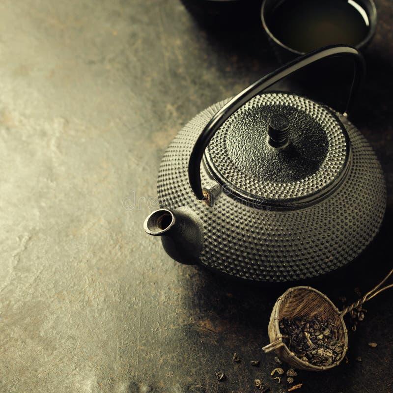 Μαύρο Teapot στο εκλεκτής ποιότητας υπόβαθρο στοκ φωτογραφίες
