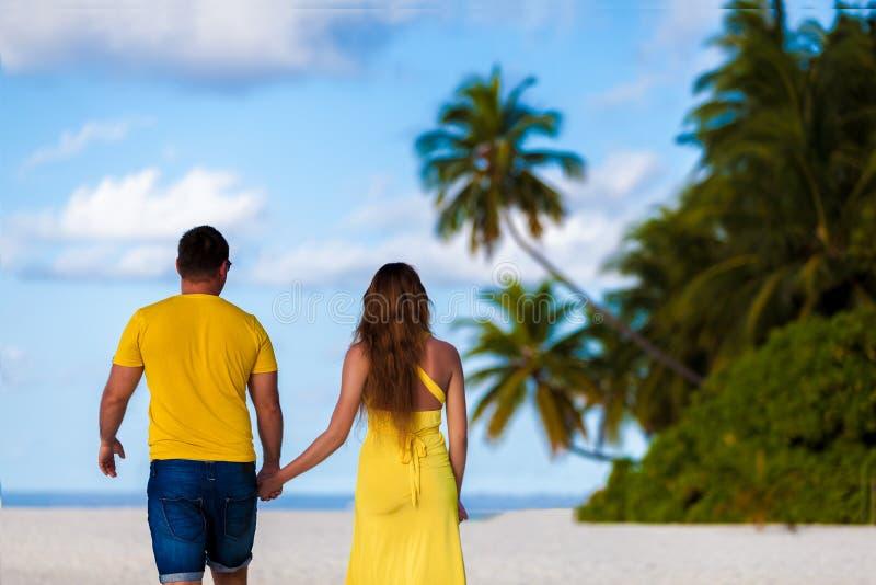 Μαλδίβες, ένα ζεύγος που περπατούν κατά μήκος της παραλίας χέρι-χέρι στοκ φωτογραφία
