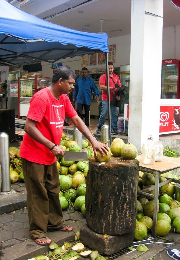 Μαλαισιανό άτομο που κόβει τις νέες καρύδες στοκ εικόνα