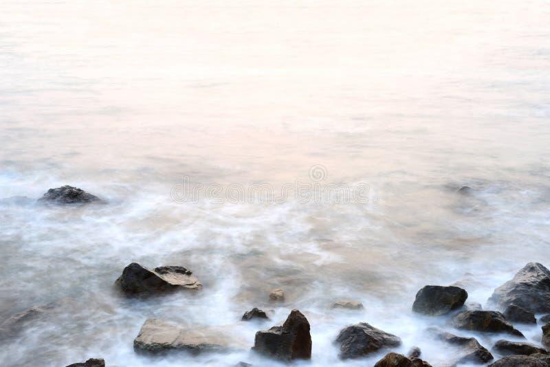Μαλακότητα υδρονέφωσης θάλασσας των παλιρροιών και του ηλιοβασιλέματος στο βράδυ με τους βράχους στοκ εικόνα