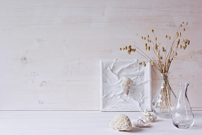 Μαλακό εγχώριο ντεκόρ Θαλασσινά κοχύλια και βάζο γυαλιού με spikelets στο άσπρο ξύλινο υπόβαθρο στοκ φωτογραφία