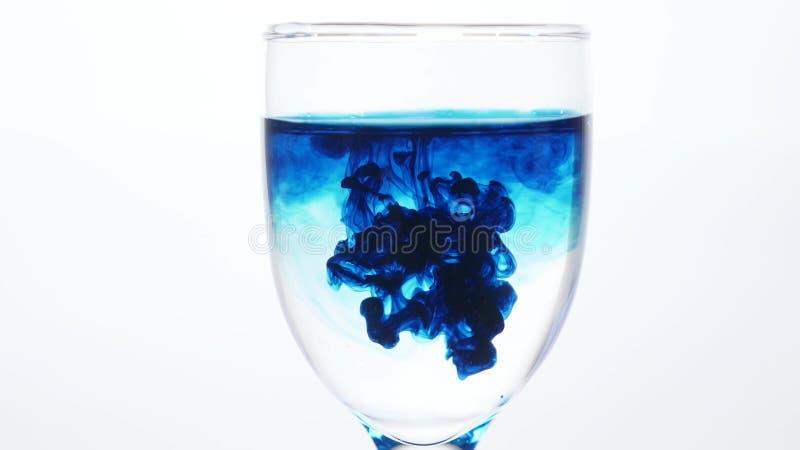 Μείωση μπλε μελανιού σε ένα ποτήρι του νερού σε ένα άσπρο υπόβαθρο Το δηλητήριο στην έννοια γυαλιού στοκ φωτογραφίες
