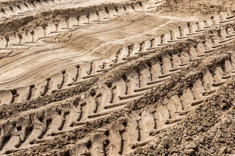 Μεγάλα ίχνη ελαστικών αυτοκινήτου φορτηγών στην ανοικτή επιφάνεια κοιλωμάτων άμμου Βαριά έννοια μηχανημάτων λατομείων στοκ εικόνα με δικαίωμα ελεύθερης χρήσης