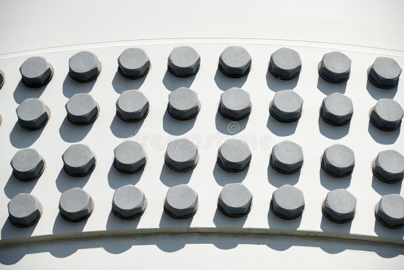Μεγάλα επικεφαλής μπουλόνια στην άσπρη κατασκευή μετάλλων ως υπόβαθρο - έννοια εφαρμοσμένης μηχανικής στοκ εικόνα με δικαίωμα ελεύθερης χρήσης