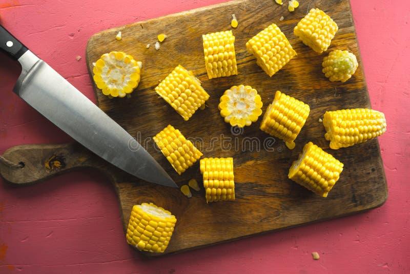 Μεγάλα κομμάτια του καλαμποκιού σε ένα τέμνον μαχαίρι πινάκων και κουζινών στοκ εικόνα με δικαίωμα ελεύθερης χρήσης