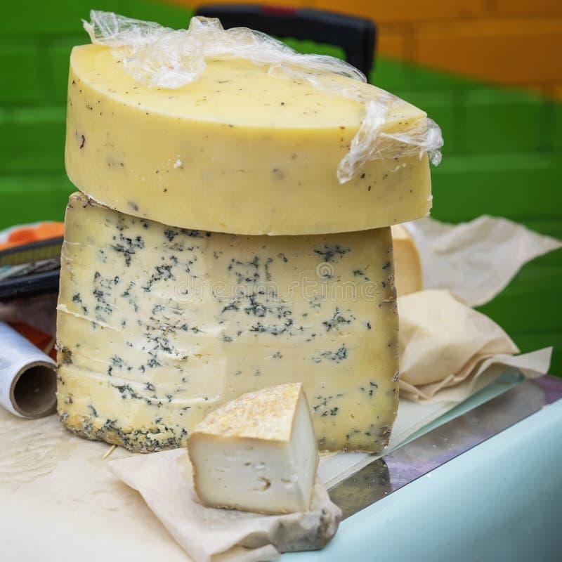 Μεγάλα κομμάτια του τυριού με την μπλε φόρμα στο μετρητή αγοράς Γαστρονομικά φίνα προϊόντα στην αντίθετη, πραγματική σκηνή αγοράς στοκ εικόνες
