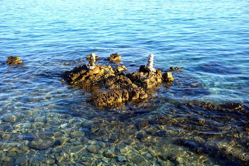 Μεγάλα πέτρα και χαλίκια που συσσωρεύονται στο ρηχό θαλάσσιο νερό τη θερινή ηλιόλουστη ημέρα στοκ εικόνα