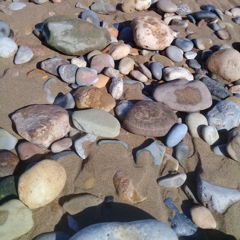 Μεγάλα ριγωτά πέτρα βράχου & πλαίσιο υποβάθρου άμμου στην παραλία στοκ εικόνες
