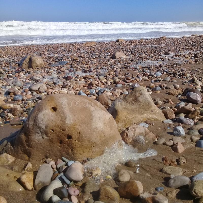 Μεγάλα ριγωτά πέτρα βράχου & πλαίσιο υποβάθρου άμμου στην παραλία στοκ εικόνα με δικαίωμα ελεύθερης χρήσης
