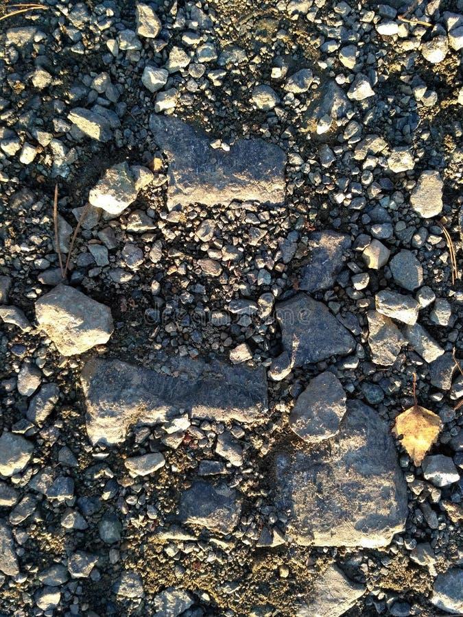 Μεγάλες και μικρές πέτρες αμμοχάλικου στο χώμα - υπόβαθρο και σύσταση στοκ εικόνα