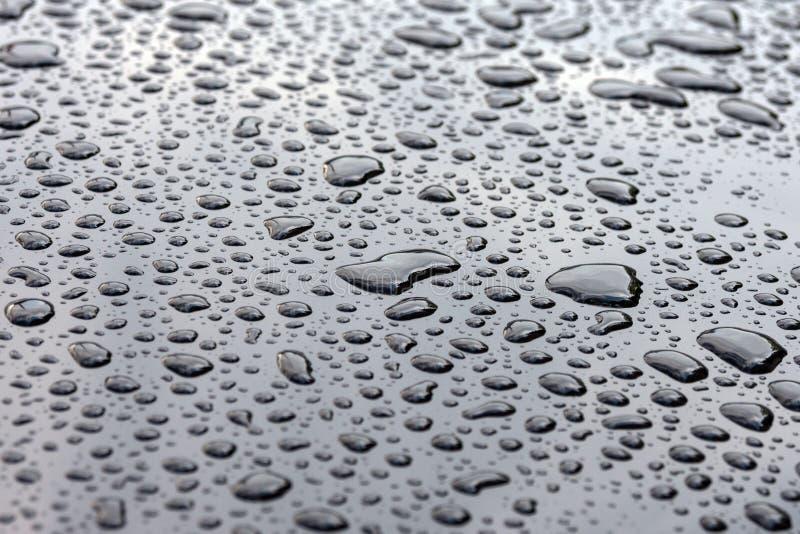 Μεγάλες σταγόνες βροχής σε μια στιλπνή μαύρη επιφάνεια r E στοκ φωτογραφία με δικαίωμα ελεύθερης χρήσης
