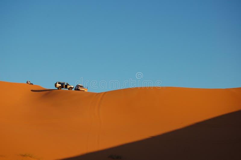 Μεγάλης ακτίνας πυροβολισμός δύο αυτοκινήτων που σταθμεύουν πάνω από τους αμμόλοφους άμμου με το σαφή μπλε ουρανό μια ηλιόλουστη  στοκ φωτογραφίες με δικαίωμα ελεύθερης χρήσης