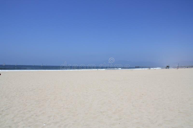 Μεγάλη άσπρη, αμμώδης παραλία κάτω από έναν μπλε ουρανό στοκ φωτογραφία