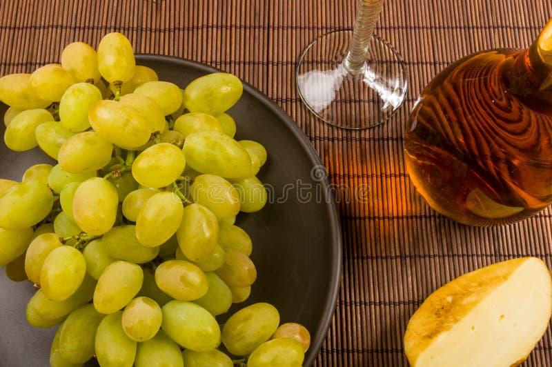 μεγάλη βούρτσα των πράσινων σταφυλιών σε ένα κεραμικό πιάτο, μια καράφα και ένα ποτήρι του κρασιού και του τυριού στοκ εικόνες με δικαίωμα ελεύθερης χρήσης