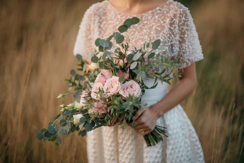 μεγάλη γαμήλια ανθοδέσμη στα χέρια της νύφης στοκ φωτογραφίες