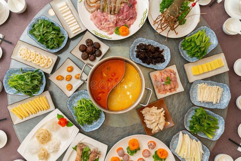 Μεγάλη διάσκεψη στρογγυλής τραπέζης με τα διαφορετικά δευτερεύοντα πιάτα σε το με τη σούπα στη μέση στοκ εικόνα