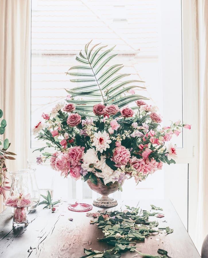 Μεγάλη εορταστική κλασσική ανθοδέσμη με τα διάφορα λουλούδια και τα φύλλα φοινικών στο βάζο δοχείων στον πίνακα στο παράθυρο στο  στοκ εικόνες με δικαίωμα ελεύθερης χρήσης