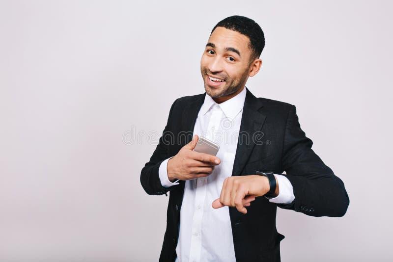 Μεγάλη επιτυχία, καλά resultas στη σταδιοδρομία του όμορφου νεαρού άνδρα στο άσπρο πουκάμισο, μαύρο σακάκι που χαμογελά στη κάμερ στοκ εικόνες
