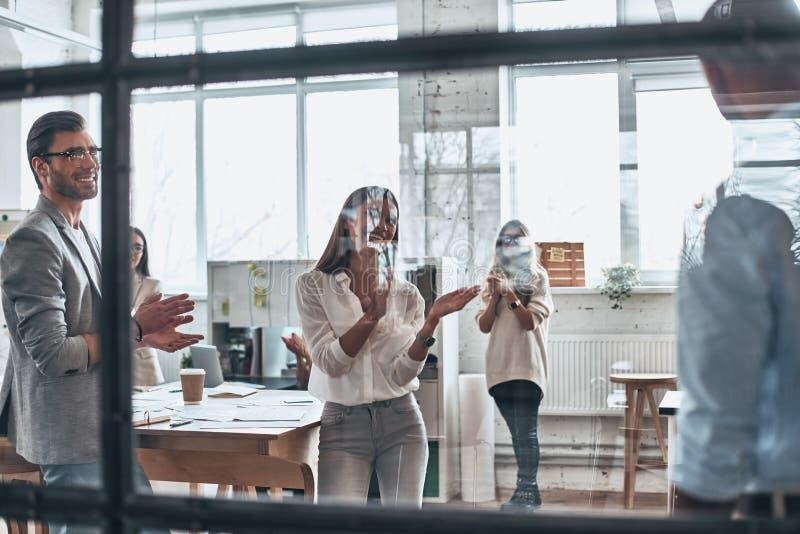 μεγάλη εργασία Ομάδα επιχειρηματιών που χτυπούν και που χαμογελούν ενώ στοκ εικόνα