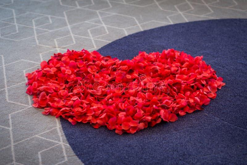 Μεγάλη καρδιά από τα κόκκινα ροδαλά πέταλα στον τάπητα γάμος λουλουδιών τελετής νυφών στοκ εικόνες
