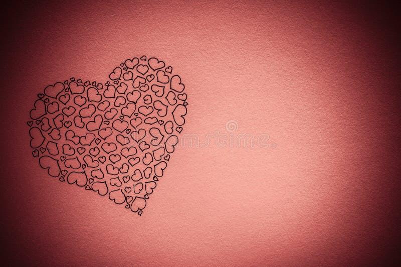 Μεγάλη καρδιά φιαγμένη επάνω από μικρές καρδιές Στρέθιμο της προσοχής της μαύρης μάνδρας σε ένα ρόδινο υπόβαθρο r Κάρτα o στοκ φωτογραφία με δικαίωμα ελεύθερης χρήσης