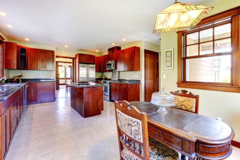 Μεγάλη ξύλινη κουζίνα chery με τον πίνακα τραπεζαριών. στοκ φωτογραφία με δικαίωμα ελεύθερης χρήσης