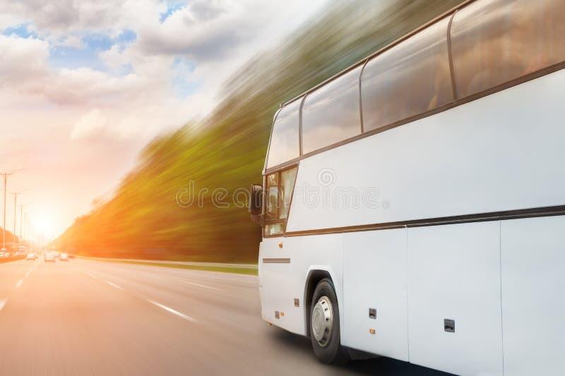 Μεγάλη οδήγηση λεωφορείων τουριστών πολυτέλειας άνετη μέσω της εθνικής οδού τη φωτεινή ηλιόλουστη ημέρα Θολωμένος δρόμος κινήσεων στοκ φωτογραφίες με δικαίωμα ελεύθερης χρήσης