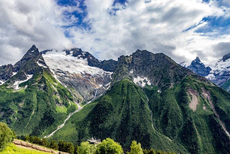Μεγάλη σειρά βουνών φύσης Καταπληκτική προοπτική του καυκάσιου βουνού ή του ηφαιστείου Elbrus χιονιού με τους πράσινους τομείς, μ στοκ φωτογραφία με δικαίωμα ελεύθερης χρήσης