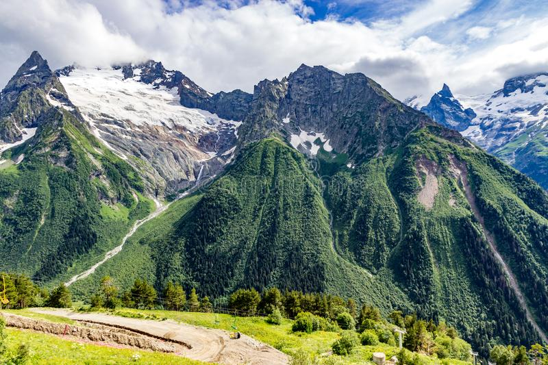 Μεγάλη σειρά βουνών φύσης Καταπληκτική προοπτική του καυκάσιου βουνού ή του ηφαιστείου Elbrus χιονιού με τους πράσινους τομείς, μ στοκ φωτογραφία