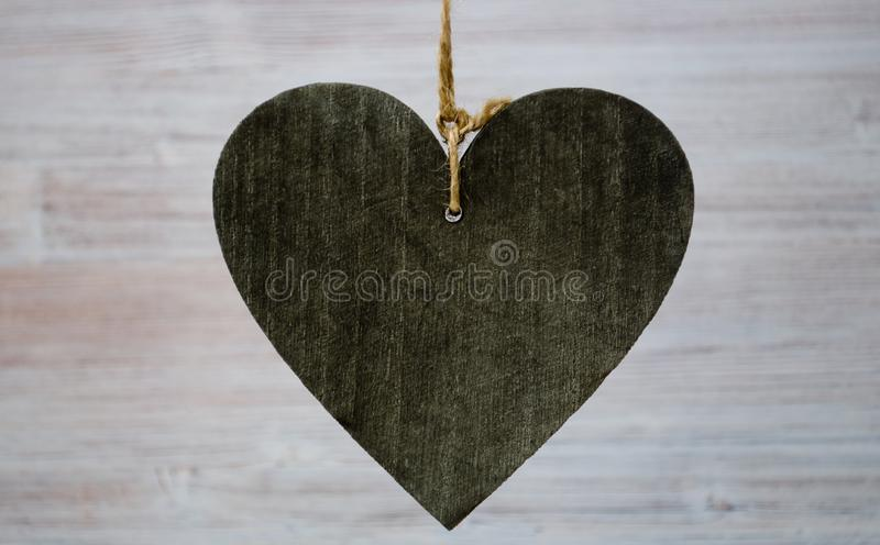 Μεγάλη σκοτεινή ξύλινη καρδιά στο ελαφρύ ξύλινο υπόβαθρο Κλείστε το επάνω και μεγάλο copyspace για το κείμενό σας στοκ φωτογραφία με δικαίωμα ελεύθερης χρήσης