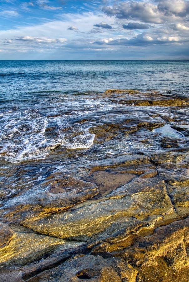 Μεγάλοι ζωηρόχρωμοι βράχοι ακριβώς κάτω από την επιφάνεια, μαλακός μπλε ουρανός κυμάτων θαλάσσιου νερού με τα σύννεφα στοκ φωτογραφία